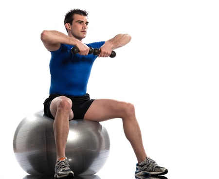 swiss ball: one caucasian man exercising workout weigth training sitting on fitness swiss ball full length isolated on white background