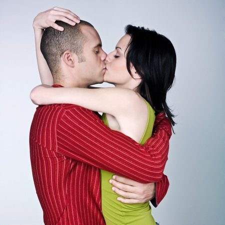 women kissing: one young couple hugging kissing on studio isolated gray background Stock Photo