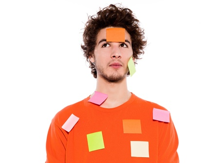 stressed out: one young thinking with adhesive notes covering caucasian man portrait in studio on isolated white background
