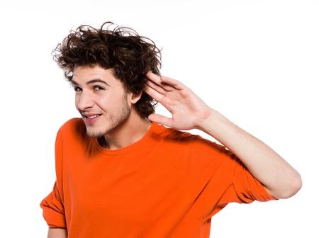 arrogancia: joven expresivo retrato del hombre cauc�sico en el estudio sobre fondo blanco con la mano en la parte posterior de la oreja Foto de archivo
