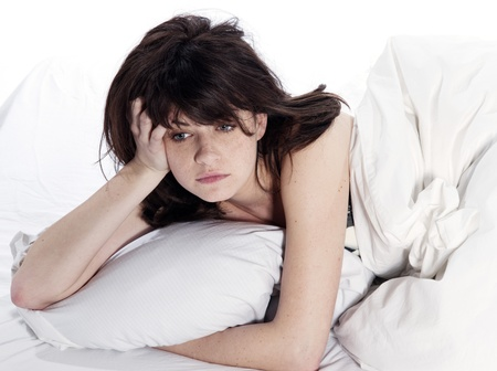 an awakening: one young woman in bed awakening tired insomnia hangover  in a white sheet bed on white background Stock Photo