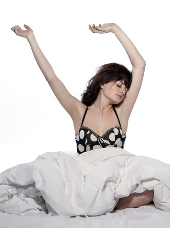 young woman in bed awakening tired insomnia hangover  in a white sheet bed on white background Stock Photo - 11752501