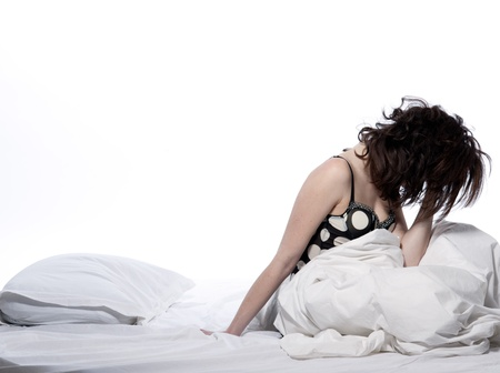 moody: one young woman in bed awakening tired insomnia hangover  in a white sheet bed on white background Stock Photo