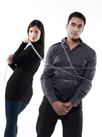 arroganza: donna, legando il suo uomo con una catena su sfondo bianco Archivio Fotografico
