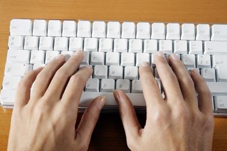 teclado de computadora: manos de la mujer escribiendo en un teclado de computadora blanco inalámbrico colocado sobre una mesa
