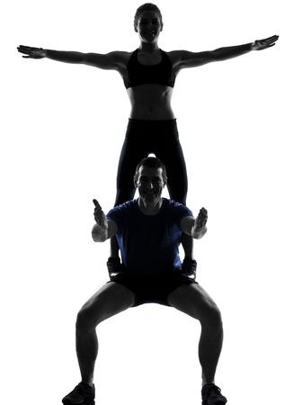 acrobacia: joven mujer al hombre el ejercicio de entrenamiento de fitness postura de ejercicios aeróbicos en el estudio de la silueta sobre fondo blanco Foto de archivo