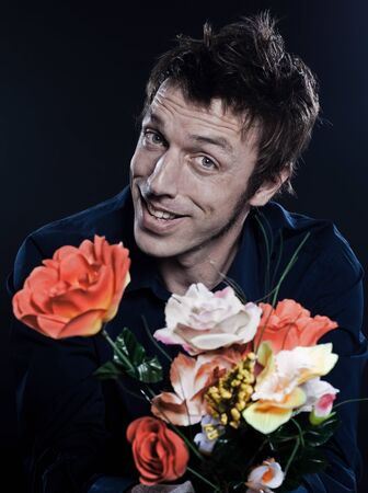 studio portrait on black background of a funny expressive caucasian man offering flowers cheerful seductor photo