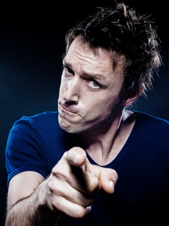 accusation: studio portrait on black background of a funny expressive caucasian man pointing menace suspicious Stock Photo