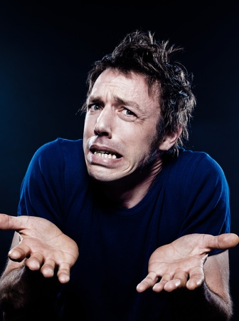desperate face: studio portrait on black background of a funny expressive caucasian man puckering interrogative hesitant Stock Photo