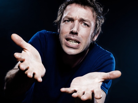 hesitancy: studio portrait on black background of a funny expressive caucasian man puckering helpless Stock Photo