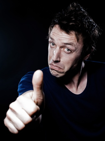 handsign: studio portrait on black background of a funny expressive caucasian man thumb up satisfied