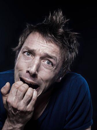 angoisse: portrait en studio sur fond noir d'un dr�le de peur expressif homme caucasien grima�ant