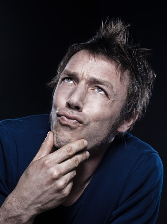 hesitancy: studio portrait on black background of a funny expressive caucasian man puckering pensive Stock Photo