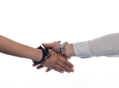 handshake with handcuffs concept agreement isolated studio on white background Stock Photo - 12710725