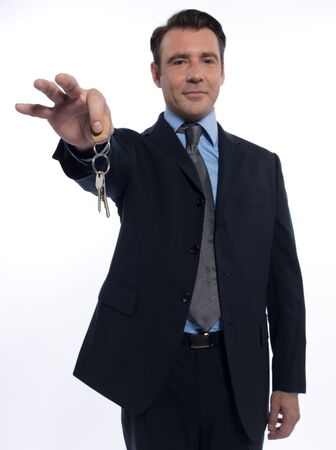 one caucasian realtor man real estate agent businessman teasing holding offering keys isolated studio on white background photo