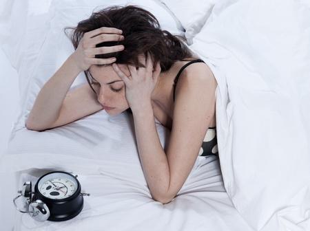 insomnio: mujer joven en una sábana blanca sobre fondo blanco Foto de archivo
