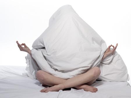 insomnio: mujer joven en una s�bana blanca sobre fondo blanco Foto de archivo