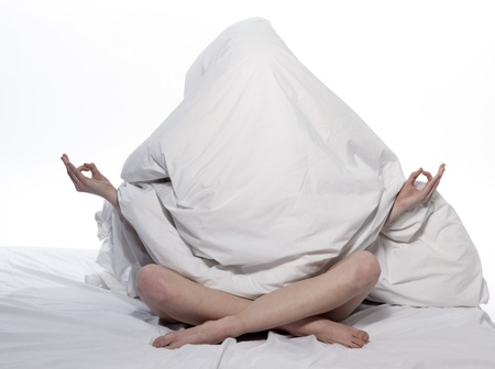 hidden: young woman in a white sheet bed on white background