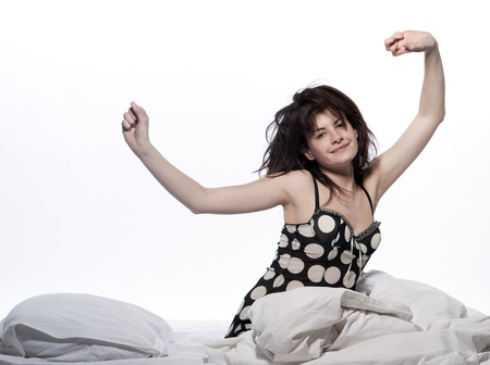 young woman in a white sheet bed on white  stretching Stock Photo - 12710781