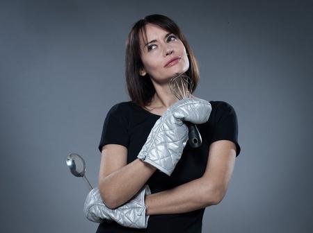 one caucasian woman thinking holding kitchen utensils isolated studio on grey background photo