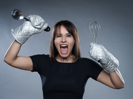 caucasian woman strain holding kitchen utensils isolated studio on grey background photo