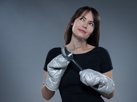 one caucasian woman thinking holding kitchen utensils isolated studio on grey background photo