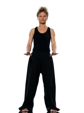 practicing: mature woman praticing tai chi chuan in studio on isolated white background
