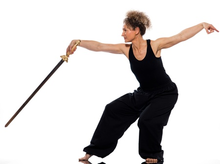 chi kung: mature woman praticing tai chi chuan with sword in studio on isolated white background