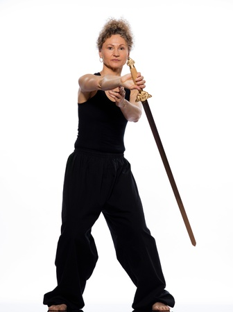 chuan: mature woman praticing tai chi chuan with sword in studio on isolated white background