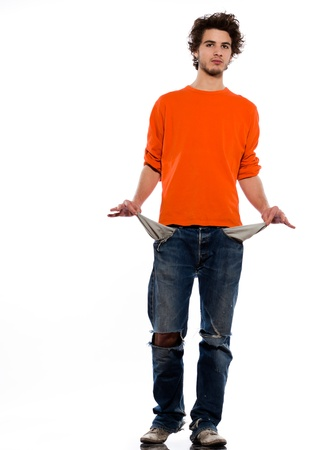 hombre pobre: un joven pobre hombre caucásico retrato que muestra bolsillos vacíos en el estudio sobre fondo blanco Foto de archivo