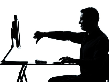 one caucasian business man computer computing thumb down displeased silhouette in studio isolated on white background photo