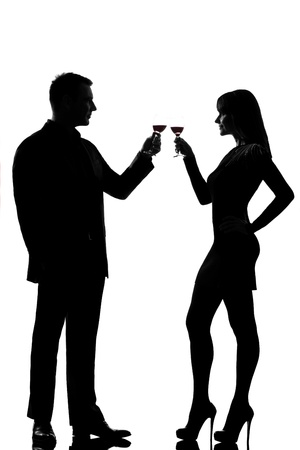 Salute: one caucasian couple man and woman drinking red wine toasting in studio silhouette isolated on white background