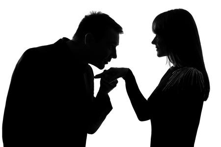 couple lit: un hombre de raza cauc�sica mujer besando la mano en el estudio de silueta aislados sobre fondo blanco Foto de archivo