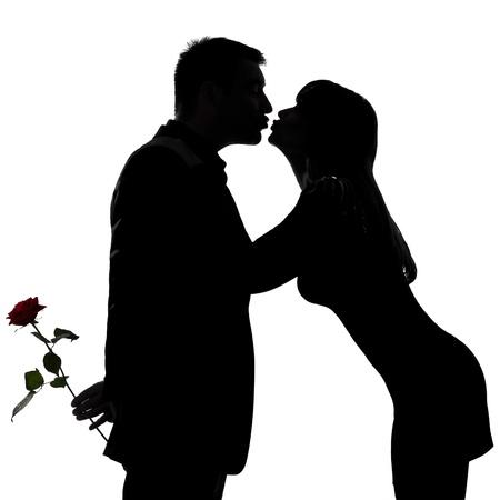 siluetas de enamorados: un hombre caucásico y una mujer besándose en el estudio de silueta aislados sobre fondo blanco Foto de archivo