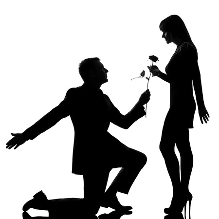 one caucasian lovers couple man kneeling offering rose flower and woman in studio silhouette isolated on white background photo