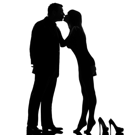 couple lit: one caucasian couple kissing man and woman barefoot tiptoe full length in studio silhouette isolated on white background Stock Photo
