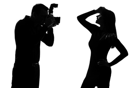 profile silhouette: one caucasian  couple man photographer photographing and woman fashion model posing in studio silhouette isolated on white background