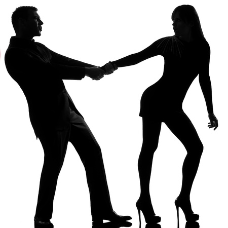 divorcing: one caucasian couple dispute separation woman leaving and man holding back in studio silhouette isolated on white background