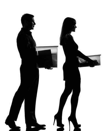 one caucasian couple man and woman walking carrying boxes happy full length in studio silhouette isolated on white background photo