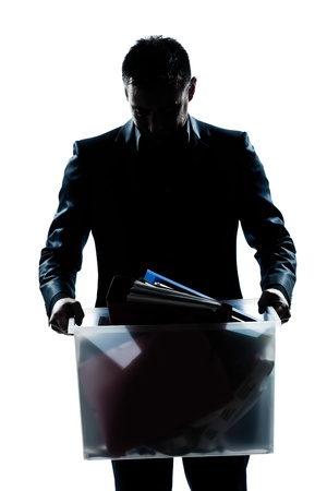 fired: one caucasian man portrait silhouette carrying heavy box in studio isolated white background