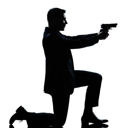 one caucasian spy criminal policeman detective man aiming shooting gun  full length silhouette in studio isolated white background Stock Photo - 12896465
