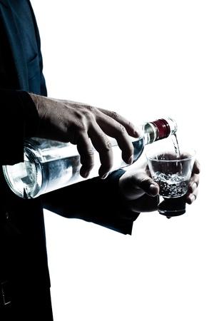 een blanke man handen close up gieten witte alcohol in een glas silhouet in de studio geïsoleerde witte achtergrond Stockfoto