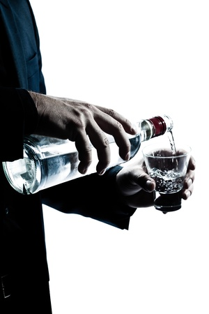 vodka bottle: one caucasian man hands close up pouring white alcohol in a glass silhouette in studio isolated white background