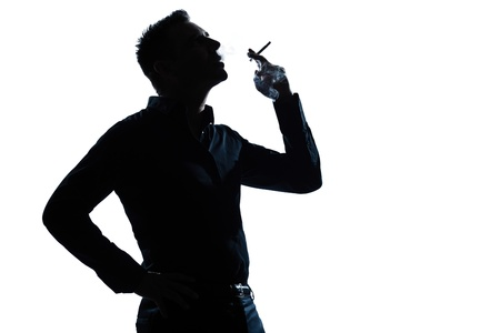 one caucasian man portrait smoking cigarette silhouette in studio isolated white background photo
