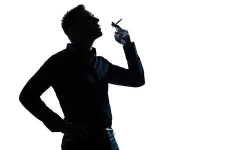 persona fumando: un hombre caucásico retrato de silueta de fumar cigarrillos en el estudio de fondo blanco aislado Foto de archivo