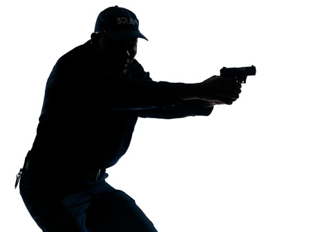 Silhouette image of an afro American mature police officer aiming a handgun in studio on white isolated background photo