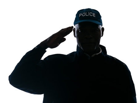 Close-up of an Afro American policeman saluting in studio on white isolated background photo