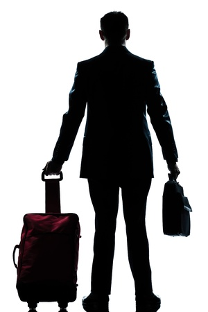 business traveler: rear view one caucasian business traveler man walking with suitcase standing  full length silhouette in studio isolated white backgroun