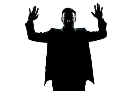 back up: one caucasian man portrait silhouette hands up in studio isolated white background