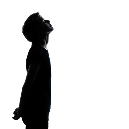 one caucasian young teenager silhouette boy or girl looking up portrait in studio cut out isolated on white background photo